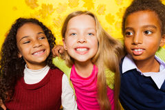 Group of children sitting on the autumn leaves Royalty Free Stock Images