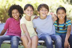 Group Of Children Sitting On Edge Of Trampoline Together Stock Images