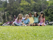 Group of children (7-9) sitting on grass in park with bicycles, smiling, portrait, surface level Stock Photos