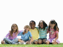 Group of children sitting on grass, smiling, portrait, cut out Stock Photography