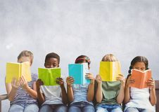 Group of children sitting and reading in front of grey background