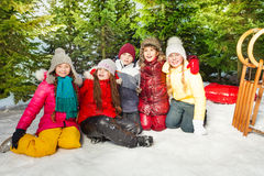 Group of children sitting on snow in winter time Stock Photography