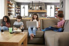 Group Of Children Sitting On Sofa Using Digital Devices Stock Images
