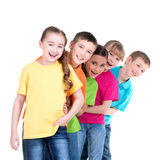 Group of children stand behind each other. Stock Image