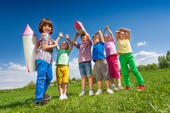 Group of children stand with paper rocket toy. Group of children standing together with paper rocket toy during sunny day in park stock images