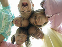 Group of children (7-9) standing in huddle, smiling, portrait, upward view Royalty Free Stock Image
