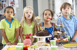 Group Of Children Standing By Table Laid With Birthday Party Food Stock Photo