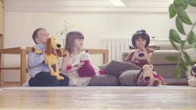 A group of children with stuffed toys. Sitting on the floor. Two girls and boy stock footage