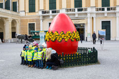 The group of children taking photo in front of large red Easter egg Stock Photography