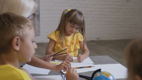 A group of children and a teacher draw on white paper using colored pencils. Primary school children drawing in the stock video footage