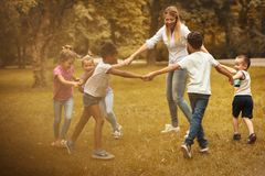Group of children with teacher playing at nature. stock photos
