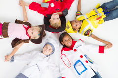 Group of children in uniforms. Group of cute little children in various workers uniforms lying on floor stock photos