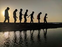 Group of Children Walking Near Body of Water Silhouette Photography Royalty Free Stock Photo