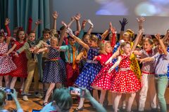 Group of children wearing bright colorful clothes and dancing on the stage. 2019.05.22, Maloyaroslavets, Russia. Group of children wearing bright colorful royalty free stock photography