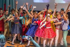 Group of children wearing bright colorful clothes and dancing on the stage. 2019.05.22, Maloyaroslavets, Russia. Group of children wearing bright colorful stock photography