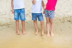 Group of children wearing casaual denim shorts having fun standing on sand at beach. Three toddler friends playing at stock photo