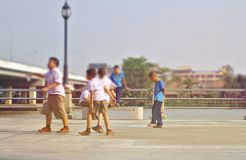 A group of children in a white school uniform and a blue sky running along the river stock photo