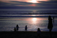 A Group of Childrenat Beach. Young Children and Mother Playing on the Beach at Sunset Royalty Free Stock Images