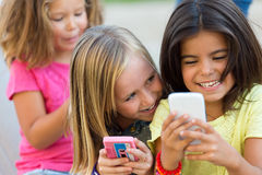 Group of childrens chatting with smart phones in the park. Royalty Free Stock Images