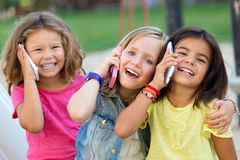 Group of childrens using mobile phones in the park. Royalty Free Stock Image