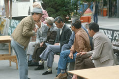 A group of Chinese men waiting at a bus stop, Royalty Free Stock Images