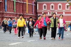 Group of chinese tourists on the Red Square. MOSCOW - SEPTEMBER 22, 2015: Group of chinese tourists walking on the Red Square. This place is considered as the Stock Image