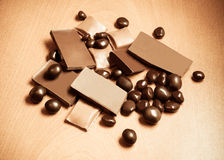 Group of chocolate pieces on wooden background. Vintage style Royalty Free Stock Photos
