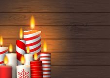 Group of Christmas burning candles on wood. Christmas theme, group of decorative red and white burning candles on dark brown wooden background, vector vector illustration