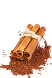 Group of cinnamon sticks on cacao powder, isolated on white background. Stock Photo