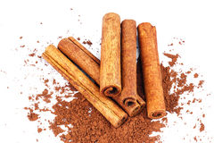 Group of cinnamon sticks on cacao powder, isolated on white background. Royalty Free Stock Photo