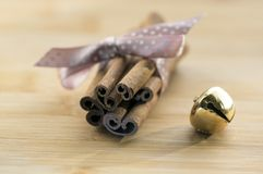 Group of cinnamon tied with light brown dotted bow, golden jingle bells. Still life Stock Images