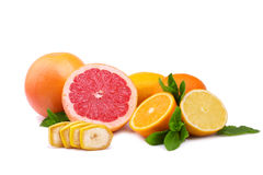 A group of citrus fruits isolated on a white background. Fresh oranges cut in half. Tropical grapefruits. Delicious chopped banana Stock Photos
