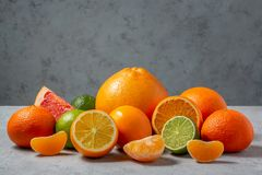 Group of citrus fruits - tangerines, lemons, limes, oranges, grapefruits on the surface of a gray table against a gray stock photography