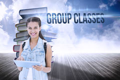 Group classes against stack of books against sky. The word group classes and student using tablet pc against stack of books against sky stock photo