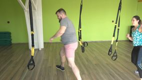 Group classes girls and men with a trainer are engaged on the TRX loops, weight loss and the development of endurance. Suspension training stock video