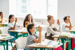 Group of classmates raising hands to answer question. During lesson royalty free stock photography