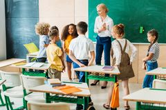 Group of classmates standing around teacher. At classroom royalty free stock image