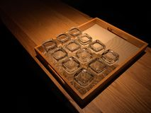 Clean drinking glasses. Group of clean drinking glasses turned upside-down within a shallow wooden service tray on a narrow wooden table, isolated against a royalty free stock photos