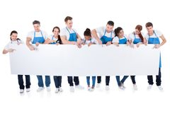 Group of cleaners holding a blank white banner. Large diverse group of cleaners or janitors wearing aprons holding a blank white banner with copy space for your royalty free stock images