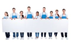 Group of cleaners holding a blank white banner. Large diverse group of cleaners or janitors wearing aprons holding a blank white banner with copy space for your Stock Photography
