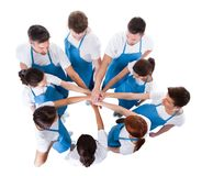 Group of cleaners stacking hands Royalty Free Stock Image