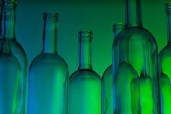 Group of clear glass wine bottles in green light Stock Photo