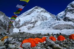 Everest climbers`tents on Khumbu glacier with prayer flags. Group of climbers ` bright color tents on the Khumbu glacier in area of Everest base camp with Royalty Free Stock Image