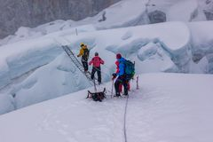 Climbers crossing a crevasse over a ladder, Island Peak, Everest Region, Nepal stock image
