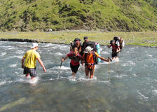 Group of climbers crossing river stock photos