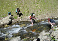 Group of climbers crossing river stock photo