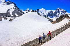Group of climbers looking at snow-capped mountains and glacier Royalty Free Stock Images