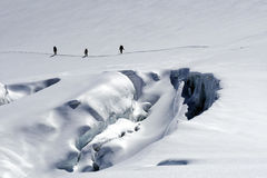 Group of climbers pass a large crevasse Royalty Free Stock Photos