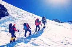 Group of climbers reaches the top of mountain peak. Climbing and. Mountaineering sport. Teamwork concept stock photography