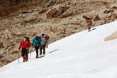 Group of Climbers walking on Snow Nepalese Porter on Background. Group of Climbers with Backpacks and climbing Gear in protective windproof Clothing walking on Stock Photo